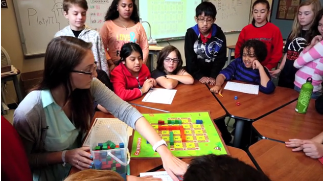 Teacher demonstrating to students around a table how to play a board game.