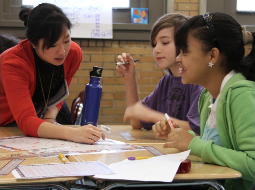 Teacher and 2 students working together at a table